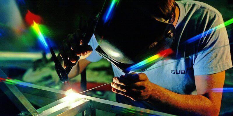 man TIG welding in shop