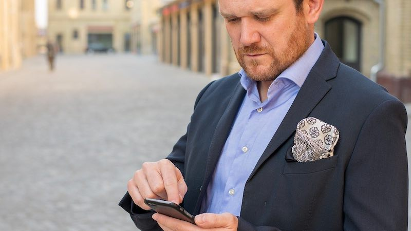 man using his phone to messages someone